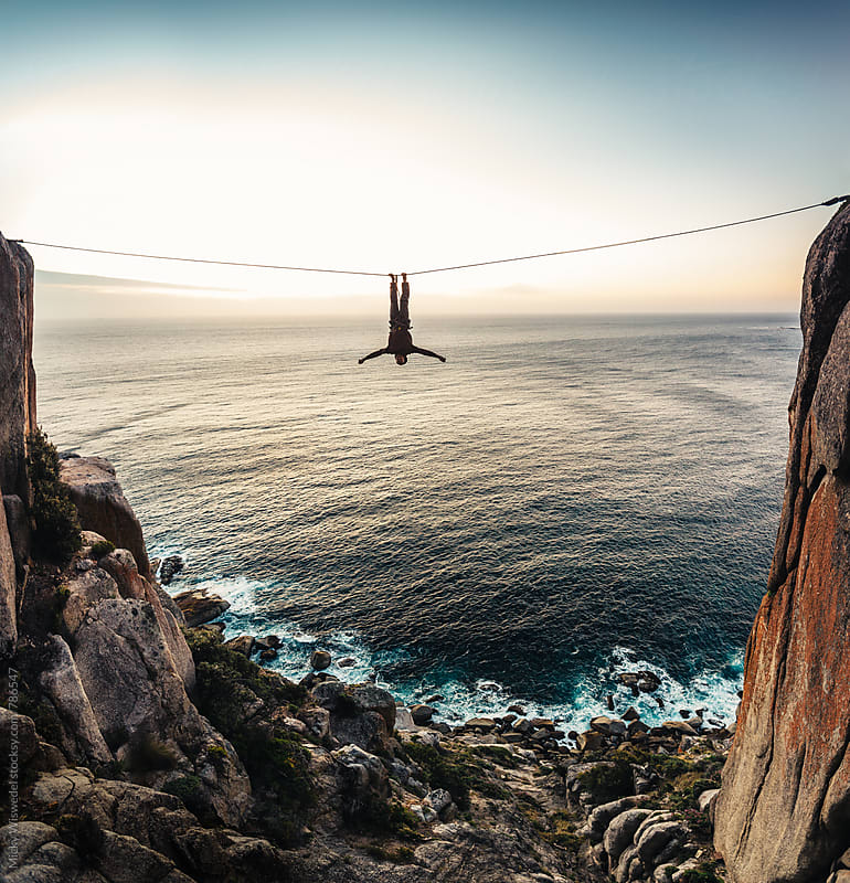 man hanging upside down from a tightrope highline between two cliffs overlooking the sea at sunset by Micky Wiswedel for Stocksy United