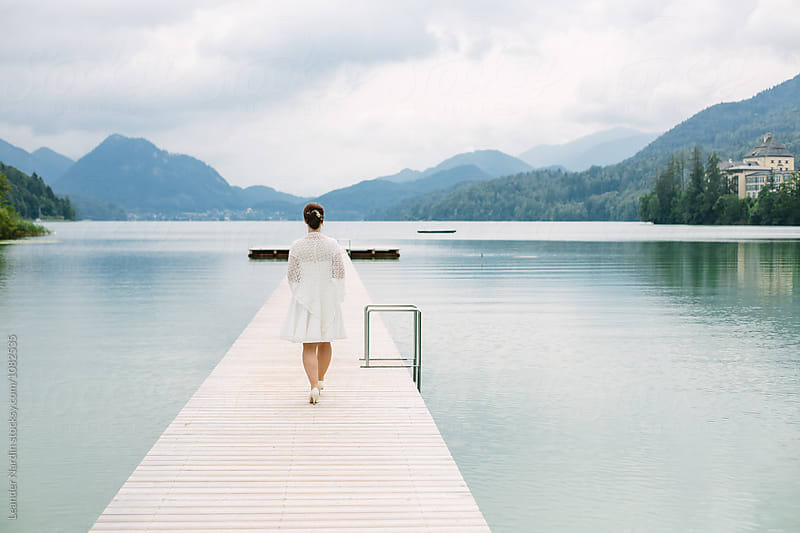 bride in white dress walking along a jetty in beautiful lake landscape by Leander Nardin for Stocksy United