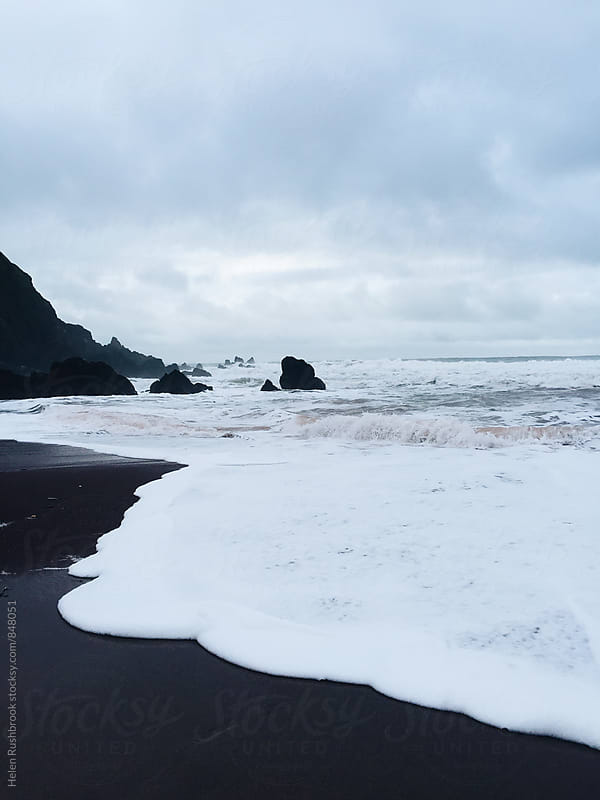Frothy waves breaking on a dramatic Welsh beach in winter. by Helen Rushbrook for Stocksy United