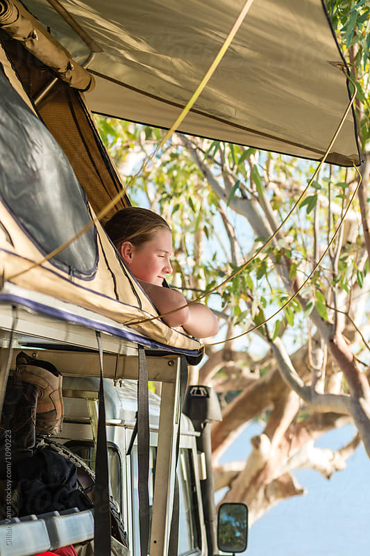 teen girl looking out from a roof top tent, NT, Australia by Gillian Vann for Stocksy United