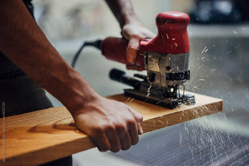 male carpenter working with electric jigsaw and wood by Juri Pozzi for Stocksy United