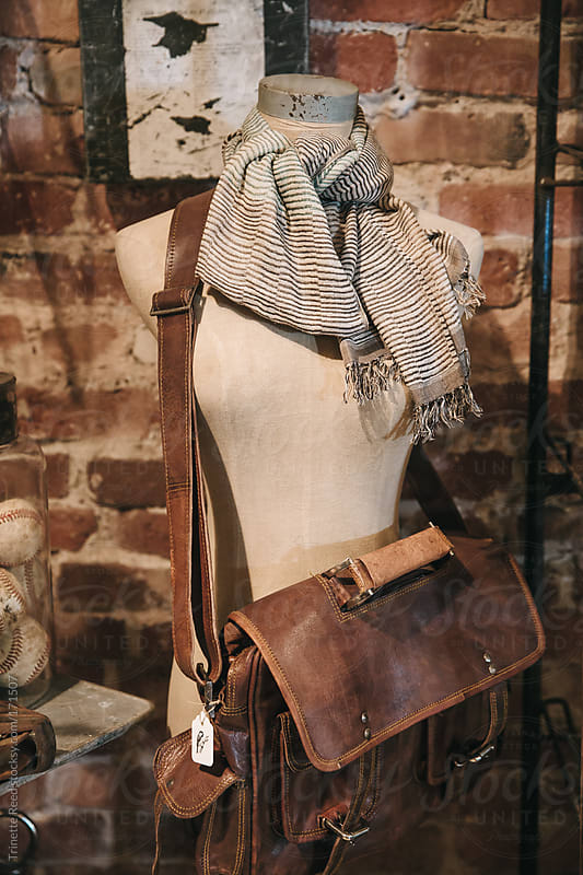 Mannequin with leather bag inside small boutique store  by Trinette Reed for Stocksy United