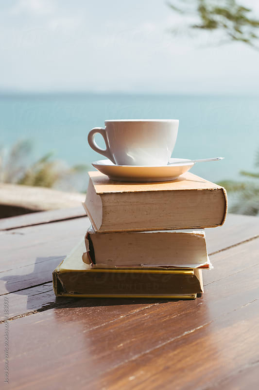 Summertime happiness - books and coffee with a ocean view by Jovo Jovanovic for Stocksy United