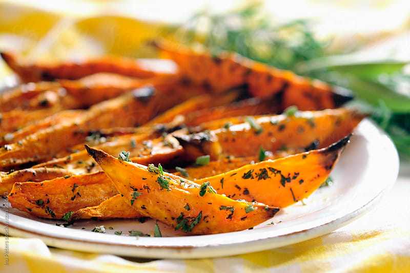 Baked herbed sweet potato wedges by Ina Peters for Stocksy United