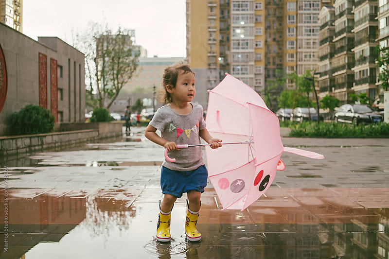 Baby girl Girl wearing rubber boots and jumping in rain puddle by MaaHoo Studio for Stocksy United