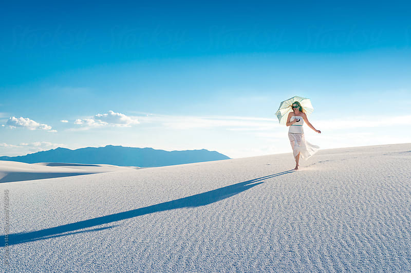 Woman Walking With Sun Umbrella In White Sands National Monumant New Mexico with Vibrant Blue Sky by JP Danko for Stocksy United