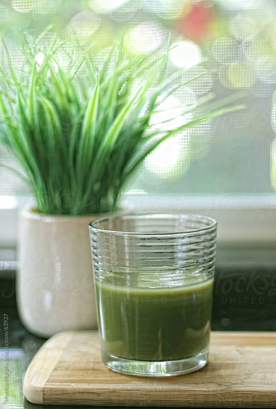 Healthy green smoothie drink on cutting board with grassy plant in the background by Monica Murphy for Stocksy United