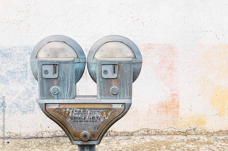 old coin-operated parking meter by a painted wall by Deirdre Malfatto for Stocksy United