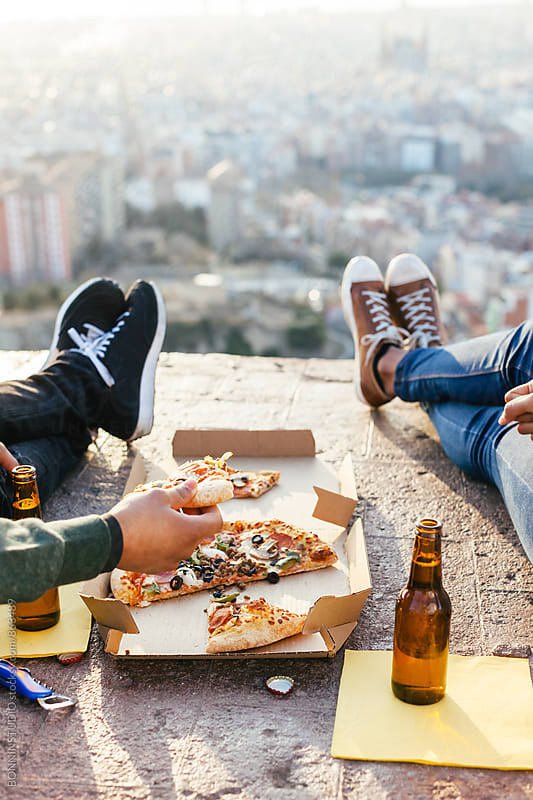 Closeup of a couple eating pizza above Barcelona. by BONNINSTUDIO for Stocksy United
