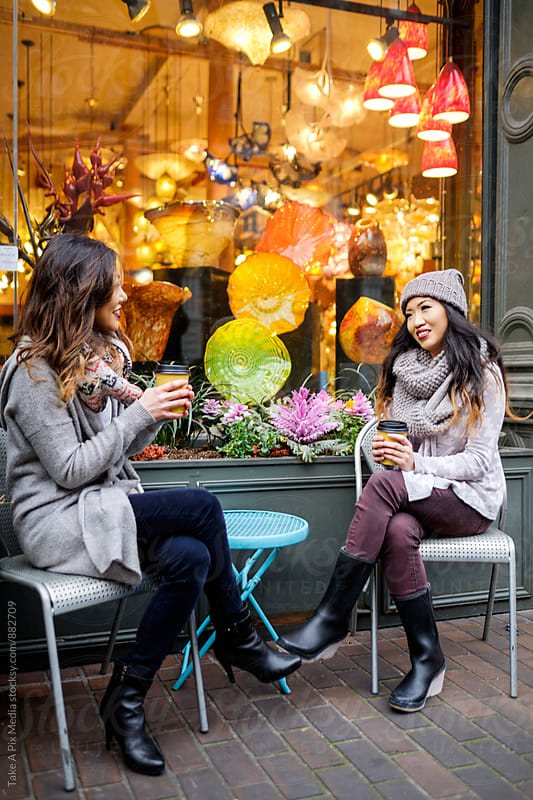 Beautiful Asian women having a conversation in front of a store by Suprijono Suharjoto for Stocksy United