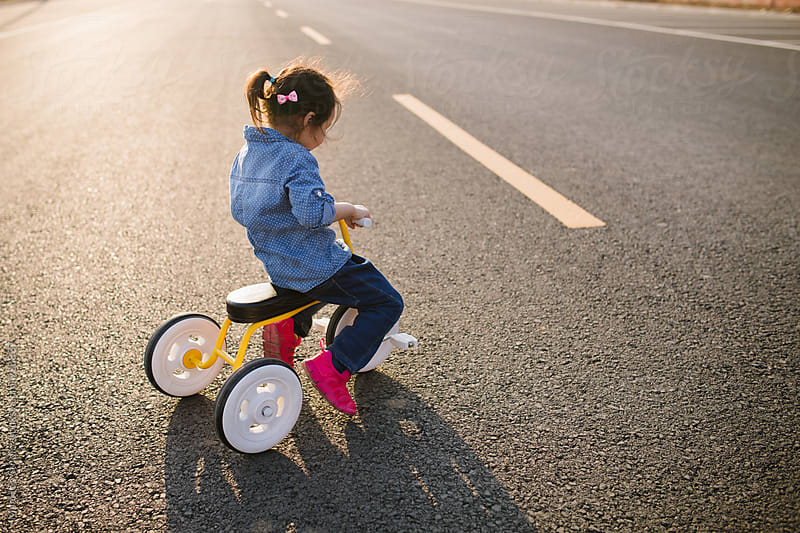 Little girl riding tricycle on road by MaaHoo Studio for Stocksy United