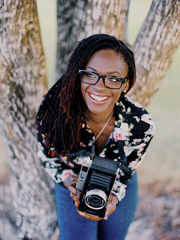 African American Female Hipster holding a vintage camera by Marlon Richardson for Stocksy United