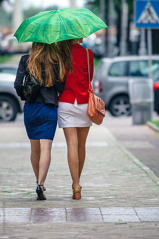 Rear view of two women friends walking under umbrella on street by Ilya for Stocksy United
