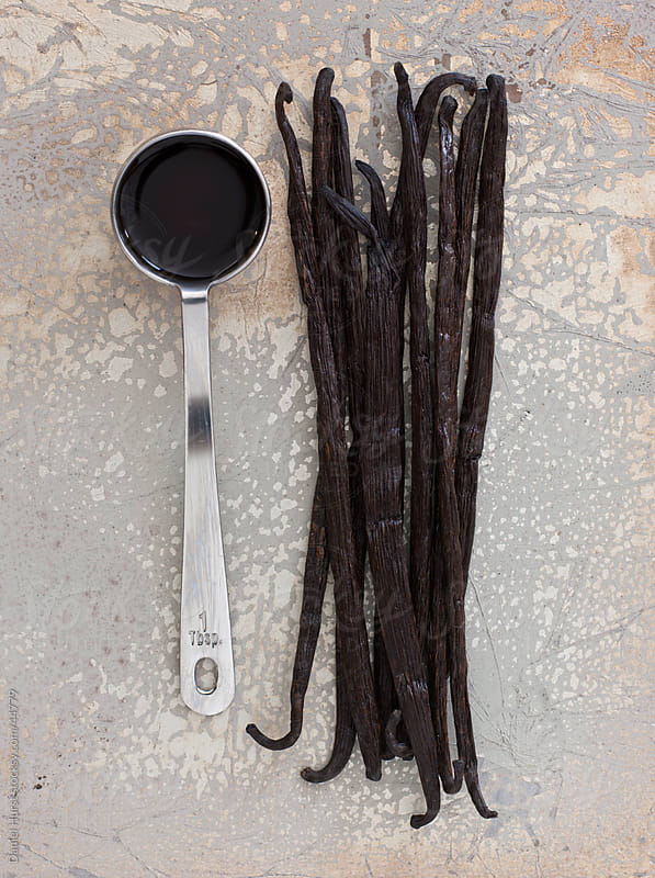 Vanilla beans and tablespoon of vanilla extract by Daniel Hurst for Stocksy United