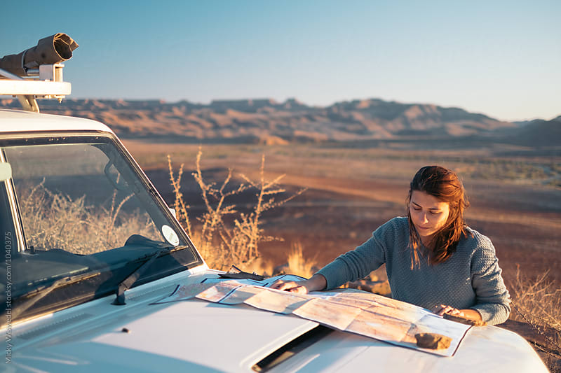 Woman reading a map on the hood of a car whilst on a road trip in the desert by Micky Wiswedel for Stocksy United