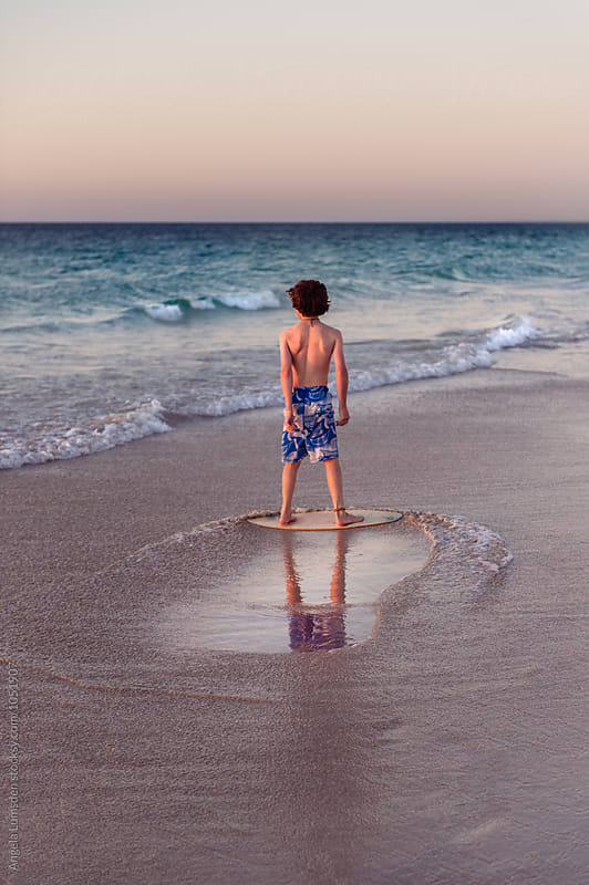 Boy skimming low waves at the beach at sunset by Angela Lumsden for Stocksy United