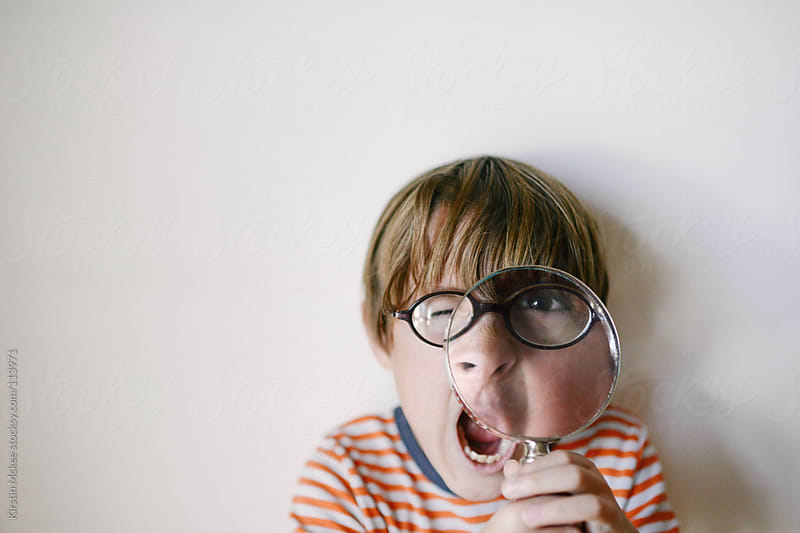 Boy holding a magnifying glass by Kirstin Mckee for Stocksy United