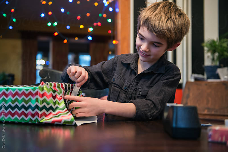 Boy does his best wrapping a Christmas gift by Cara Dolan for Stocksy United