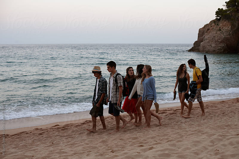 Group of teenagers walking on a mediterranean beach after sunset by Miquel Llonch for Stocksy United