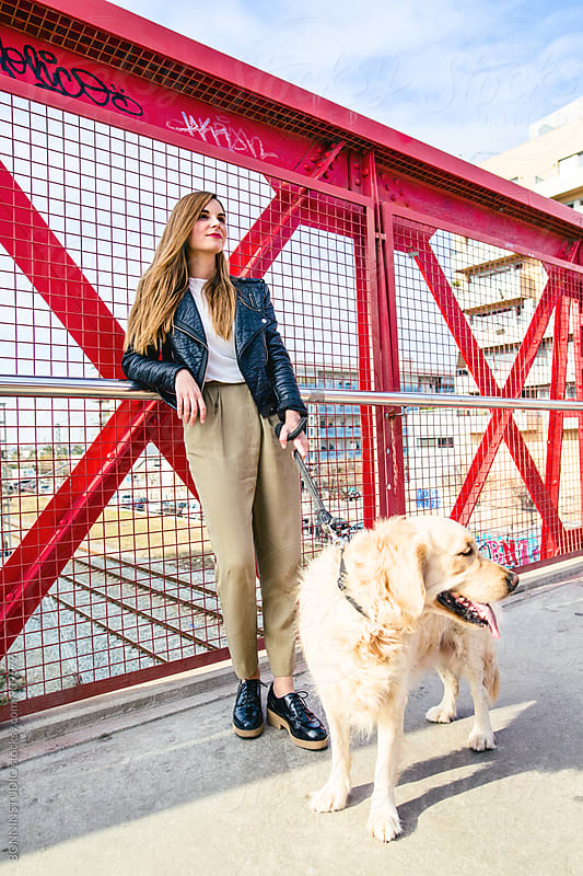 Woman and her dog standing on a bridge. by BONNINSTUDIO for Stocksy United