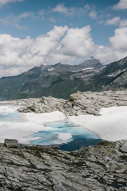small blue glacier lake in high alpine landscape by Leander Nardin for Stocksy United