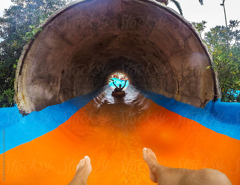 Man throwing down a slide at a water park by ACALU Studio for Stocksy United