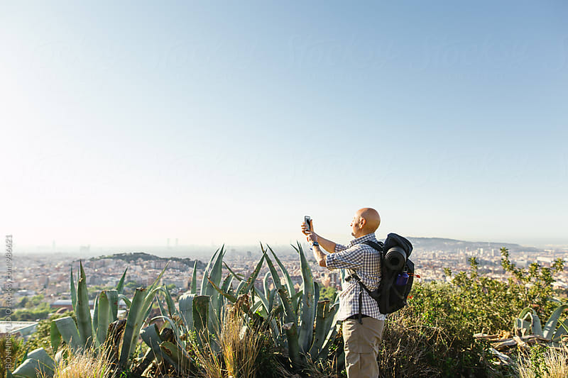 Hiker senior man taking a photo of the cityscape view. by BONNINSTUDIO for Stocksy United