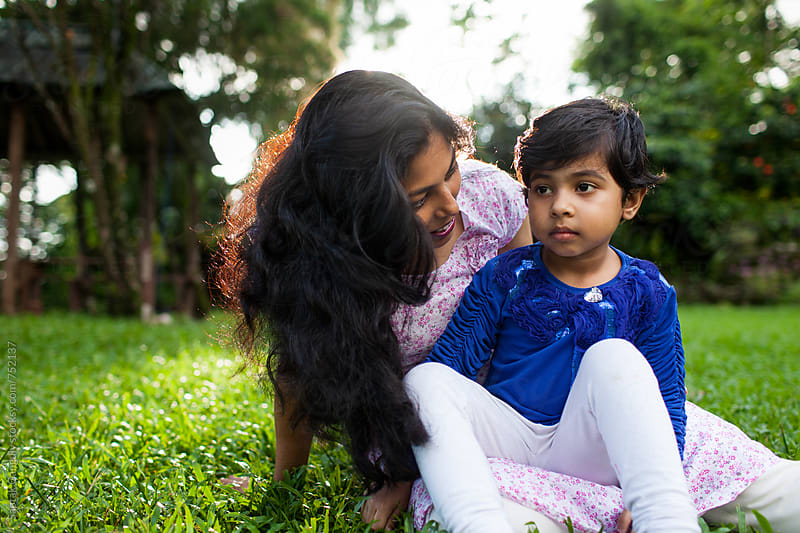Mother consoling her little daughter sitting in the lawn by Saptak Ganguly for Stocksy United