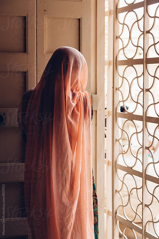 Anonymous women covered in a pale pink sari looking out of a window by Maresa Smith for Stocksy United