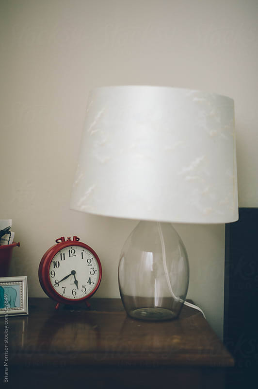 Red Alarm Clock and Lamp on a Night Stand by Briana Morrison for Stocksy United