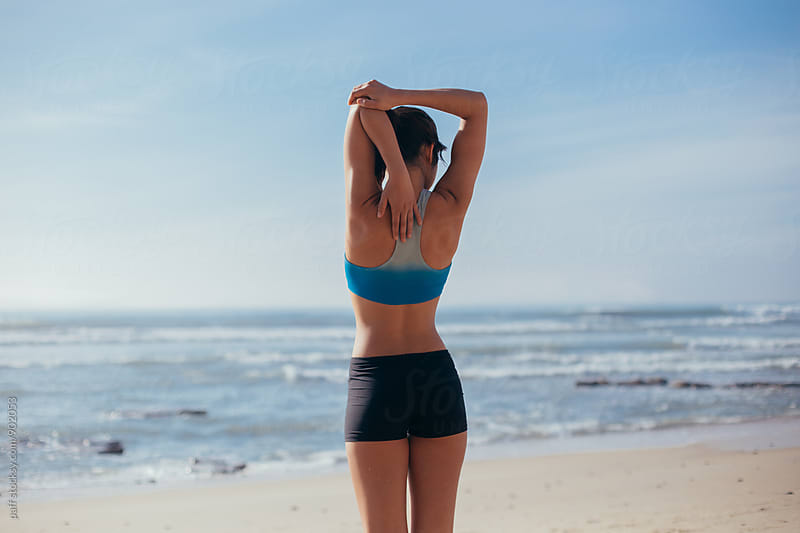 Female athlete stretching her arm on the beach looking at the ocean by paff for Stocksy United