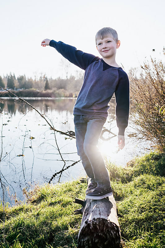 Portrait of a happy boy balancing and walking on a log by Suprijono Suharjoto for Stocksy United
