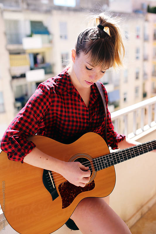 Young woman playing the guitar by Lucas Ottone for Stocksy United