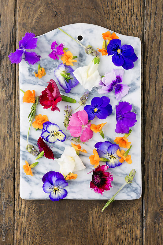 Edible flowers on marble chopping board by Kirsty Begg for Stocksy United