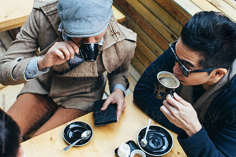 Two Well-Dressed Young Asian Men Having Coffee in Bright Café by VISUALSPECTRUM for Stocksy United