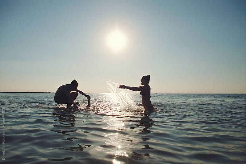 Friends having fun in the ocean on a sunny day by Denni Van Huis for Stocksy United