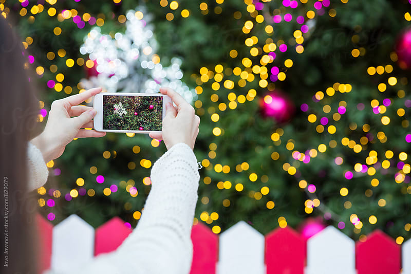 Woman taking a photo of a Christmas tree by Jovo Jovanovic for Stocksy United