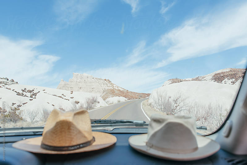 Brimmed hats on a dashboard with white desert in background by Jeremy Pawlowski for Stocksy United