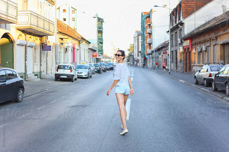 Handsome woman walking in the middle of the street in the city by Marija Mandic for Stocksy United