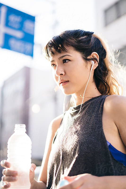 Asian woman drinking a bottle of water after running by Juri Pozzi for Stocksy United