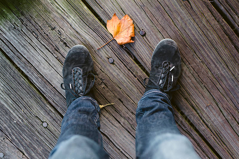 Looking down on a leaf between two feet wearing sneakers. by Holly Clark for Stocksy United