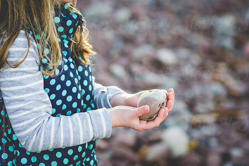 Girl holding rock on a rocky beach by Lindsay Crandall for Stocksy United