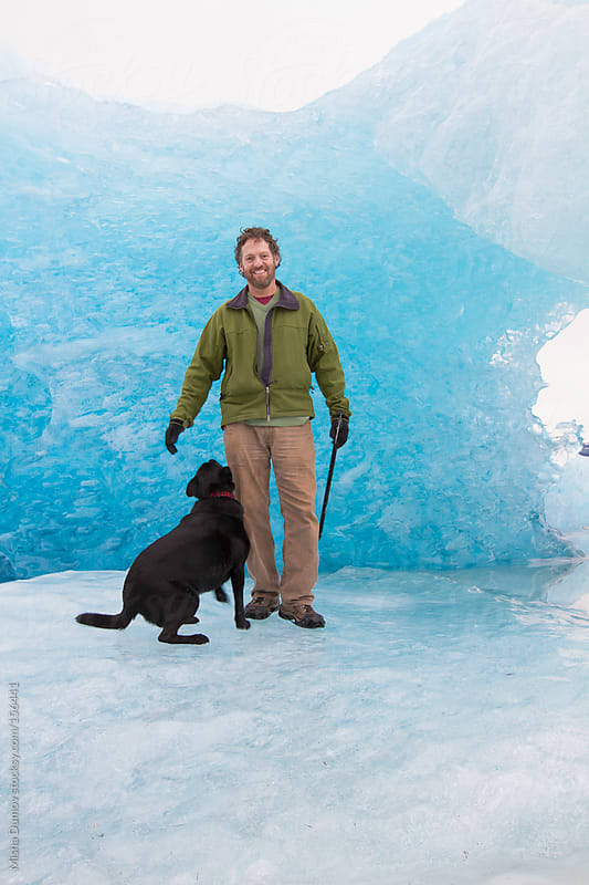 Man playing with dog on a frozen lake by an iceberg by Mihael Blikshteyn for Stocksy United