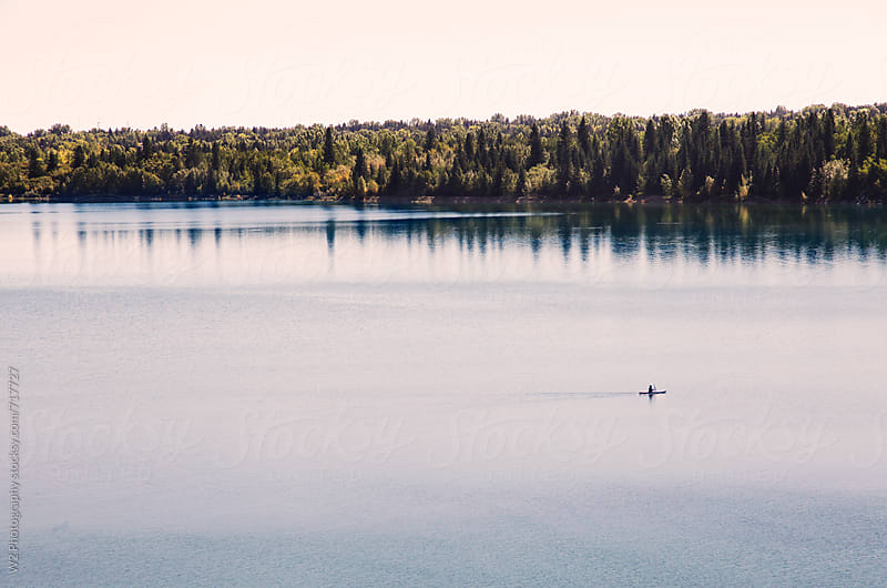 View of a lake with a kayaker. by W2 Photography for Stocksy United