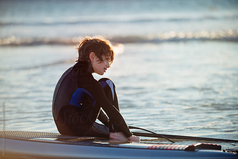 Boy sitting on a paddle board at sunset by Angela Lumsden for Stocksy United