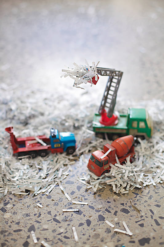 close up of toy trucks filled with pretend snow / shredded paper by Natalie JEFFCOTT for Stocksy United
