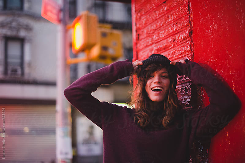 Playful young woman adjusting hat by Lauren Naefe for Stocksy United
