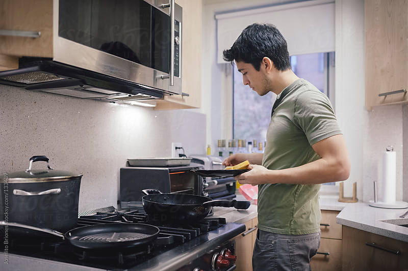 Young Hispanic - Latino Male Student Using Toaster Oven in Kitchen of New York Apartment by Joselito Briones for Stocksy United