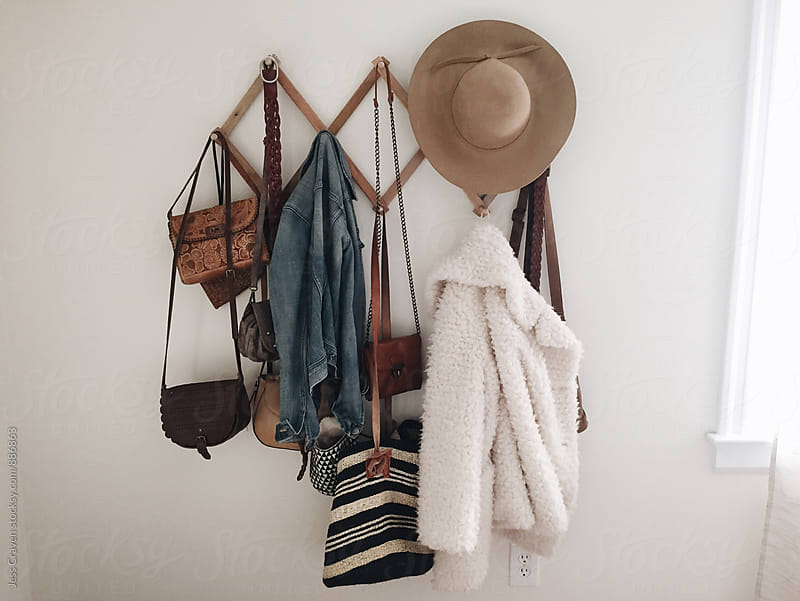 Clothes and purses hanging on accordion wall hook organizer by Daring Wanderer for Stocksy United