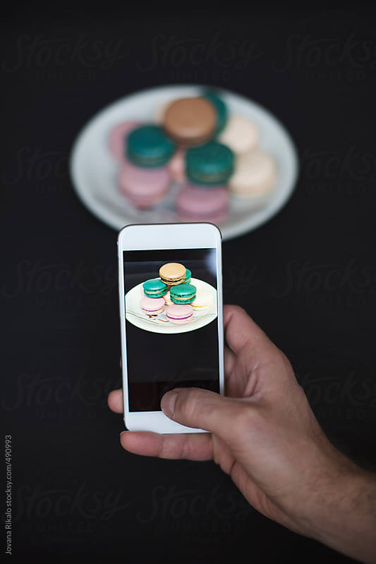 Man taking photos of a french macaroons by Jovana Rikalo for Stocksy United